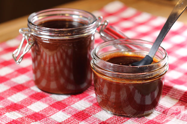 Gluten-Free Food: Two canning jars of Homemade BBQ Sauce on a red checker placemat.