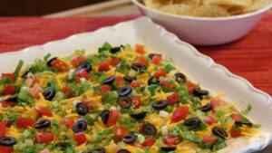 Classic Easy Taco Dip on a serving plate topped with shredded cheddar cheese, lettuce, roma tomatoes, sliced black olives, and green onions.