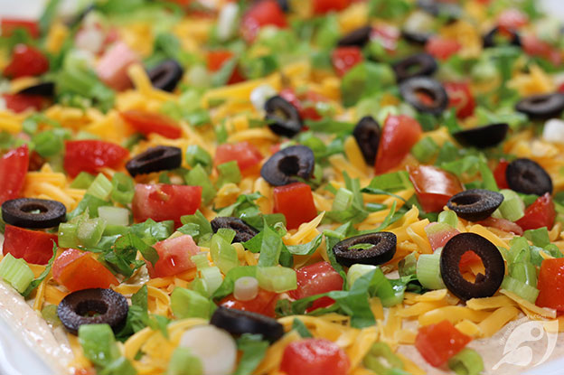 Closeup of Classic Easy Taco Dip on a serving plate topped with shredded cheddar cheese, lettuce, roma tomatoes, sliced black olives, and green onions.