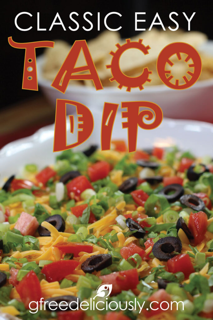 Pinterest image of Classic Easy Taco Dip on a serving plate topped with shredded cheddar cheese, lettuce, roma tomatoes, sliced black olives, and green onions.