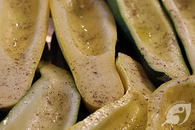 Zucchini and summer squash cut in half, seeds removed, and placed on a shallow pan then drizzled with roasted garlic grapeseed oil and sprinkled with salt and pepper.