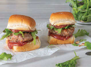 Two Sage Turkey Sliders with Cranberry Mayo on parchment paper