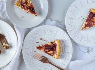 four scalloped fancy plates each with a slice of Cranberry Swirl Cheesecake