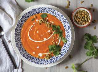 Carrot Ginger Soup in a bowl garnished with Pepitas and cilantro