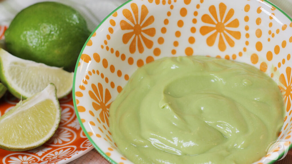 Dairy-Free Avocado Cream closeup with limes in the background