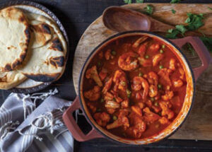 Berbere Shrimp Curry in a pot shown with flatbread on a plate