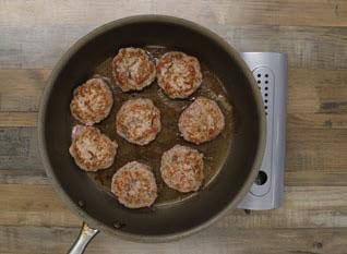 Sage Turkey Slider patties cooking in a skillet in oil.