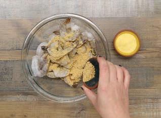 adding cornmeal and Blazin' Buffalo Blend to raw shrimp in a bowl