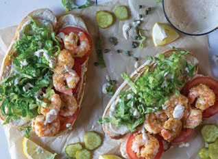 layering the lettuce, tomato and shrimp onto the baguettes