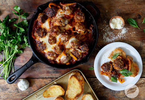 Meatball Skillet Bake in a cast iron skillet alongside crusty bread and a serving on a plate