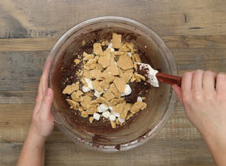 Fold in the mini marshmallows and graham crackers (setting aside a few pieces of graham cracker and a few mini marshmallows for garnish)