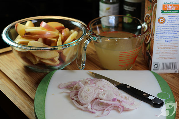 Sliced apples in a bowl, Sliced shallots on a cutting board, 1 cup chicken stock on a measuring cut