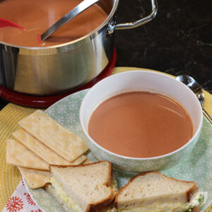 Bowl of homemade tomato juice on a plate with crackers and an egg salad sandwich