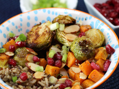 Roasted Veggie & Wild Rice Buddha Bowl with scallions and pomegranate in the background