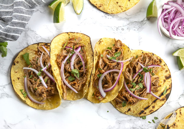 Four Enchilada Pork Tacos with lime and onions