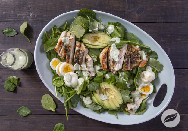 Green Goddess Chicken Cobb Salad on a flat dish with green goddess dressing on the side