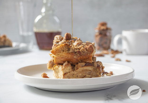 Chai French Toast Bake on a white plate with maple syrup drizzling on top