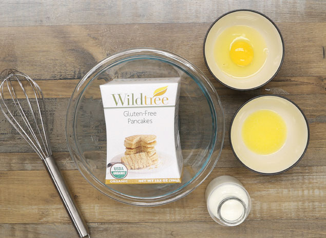 Wildtree Gluten-Free Pancakes Mix package next to bowls with egg, milk and melted butter