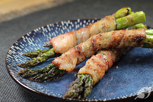 Grilled Bacon Wrapped Asparagus bundles on a blue plate.