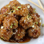 Baked Orange Chicken Meatballs on a plate with chopsticks.