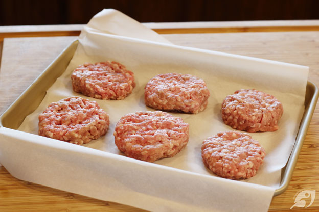 Six sausage patties on parchment with space between to freeze individual portions