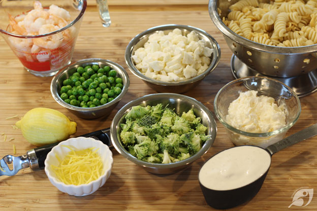 While the pasta is cooking, rinse and drain the broccoli and cauliflower under cool water. You'll want to make sure to drain it well, cut off any bad spots, then cut down the florets into small pieces. Finally, zest the lemon and measure out the remaining ingredients.