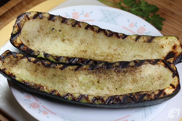 Zucchini from the grill on a plate ready to be stuffed with the veggie mixture