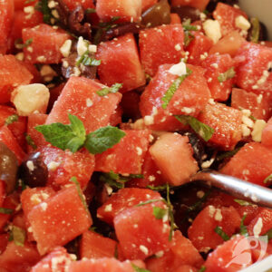 A serving bowl with Watermelon, Mint, and Feta with Kalamata Olives